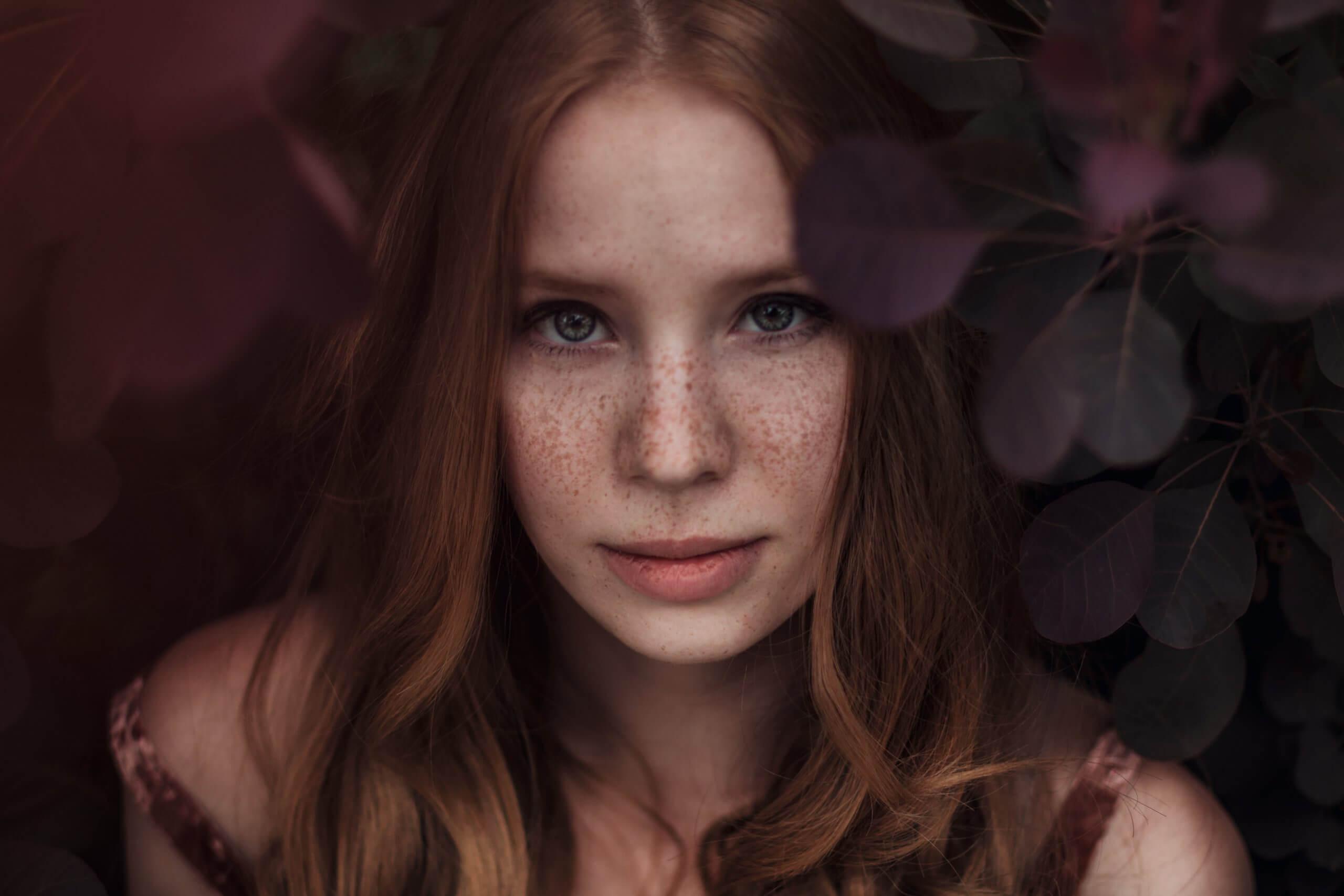Porträtfoto von einem rothaarigen Mädchen vor einem Busch